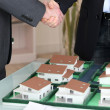 Handshake over a model housing estate — Stock Photo