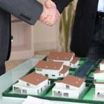 Handshake over a model housing estate — Stock Photo