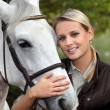 Blond woman with her horse - Foto Stock
