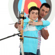 Stock Photo: Mteaching archery to boy