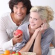Couple eating fruit from basket in kitchen — Stock Photo
