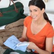 Young woman preparing travel bag - Stock Photo