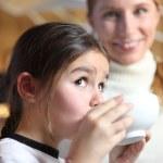 Little girl drinking from breakfast bowl — Stock Photo