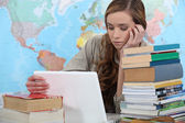 Young female student with laptop surrounded by books — Stock Photo