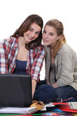 Girls sitting on the floor with computer — Stock Photo