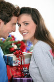 Couple stood by Christmas tree and gifts — Stock Photo