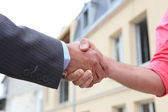 Couple shaking hands outside a house — Stock Photo
