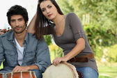 Couple playing bongo drums outdoors — Stock Photo