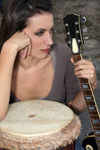 Moody brunette holding guitar and bongo — Stock Photo