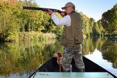 Hunter in boat — Stock Photo