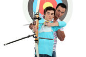 Man teaching archery to a boy — Stock Photo