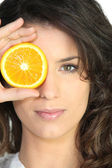 Woman covering eye orange — Stock Photo