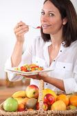 Health conscious brunette eating fruit salad — Stock Photo