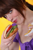 Woman eating burger and chips — Stock Photo