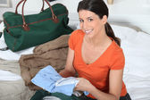 Young woman preparing travel bag — Stock Photo