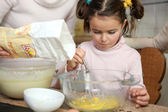Young girl learning how to cook — Stock Photo