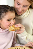 Girl and mom eating pancakes — Стоковое фото