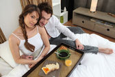 Lucky couple having breakfast in bed — Stock Photo