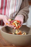 Woman gathering vegetable peeling in a bowl — Stock Photo