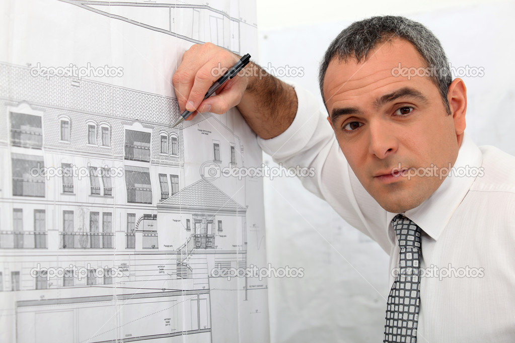 Architect examining a blueprint in detail  Stock Photo #10393430