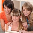 Stock Photo: Three girls looking in shopping bags