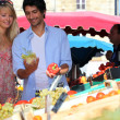 Foto Stock: Young couple at market stall
