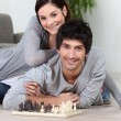 Couple laying on the floor playing chess — Foto de Stock