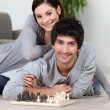 Couple laying on the floor playing chess — Stockfoto
