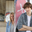 Urban couple stood by gratified wall — Stock Photo