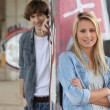 Attractive couples stood by graffiti covered wall - Stok fotoğraf