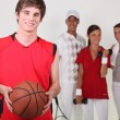 Royalty-Free Stock Photo: A basketball player posing with other athletes
