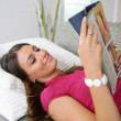 Woman laying reading magazine — Stock Photo