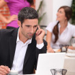 Businessman in a restaurant with a laptop — Stock Photo