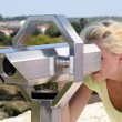 Stock Photo: Womlooking through telescope
