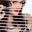 Attractive woman peeking through some blinds - Stock Photo