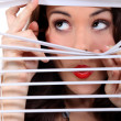 Stock Photo: Cute brunette spying through blinds.