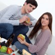 Young couple eating burgers on sofa — Stock Photo