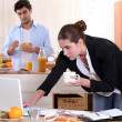 Stock Photo: Womworking while eating breakfast