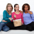 Three woman eating popcorn whilst watching film — Stock Photo