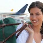 Молодая женщина, улыбаясь с сумкой — Стоковое фото