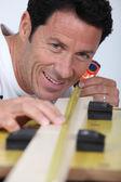Carpenter measuring wood lath — Stock Photo