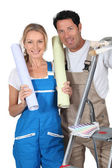 Man and woman with rolls of wallpaper and stepladder — Stock Photo