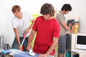 Three young male house-mates cleaning — Stock Photo