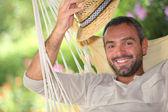 Man with hat on hammock — Stock Photo