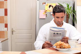 Man reading his newspaper over breakfast — Stock Photo