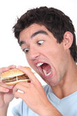 Young man taking an exaggerated bite out of a hamburger — Stock Photo