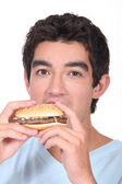 Man eating cheeseburger — Stock Photo