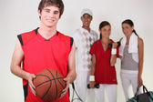A basketball player posing with other athletes — Stock Photo