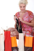 Kobiety na kolanach przez zakupy powrotem pełen bielizna — Zdjęcie stockowe