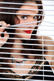 Donna attraente sbirciando attraverso alcuni ciechi — Foto Stock